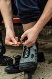 Man putting on roller skates outdoor. Royalty Free Stock Image