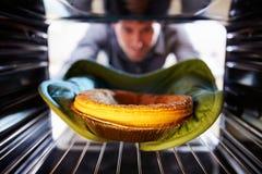 Man Putting Savoury Pie Into Oven To Bake Stock Image
