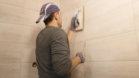 Man putting seams of beige tiles on the wall. Close up. slow motion stock video footage