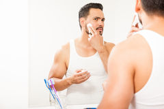 Man putting shaving cream on his face Stock Photography