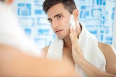 Man putting on shaving cream. Sexy handsome young man putting on shaving cream on cheek Royalty Free Stock Image