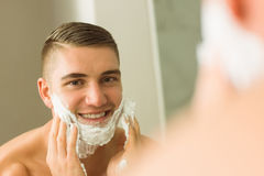 Man putting shaving foam on face Stock Photo