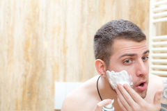 Man is putting shaving foam on the face. Shirtless man is putting shaving foam on his face to begin to trim his beard, as in every morning stock image
