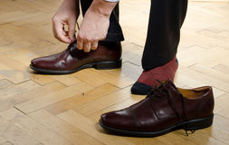 Man putting on shoes Stock Images