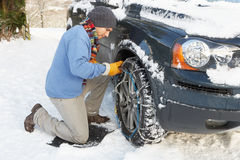 Man Putting Snow Chains Onto Tire of a car