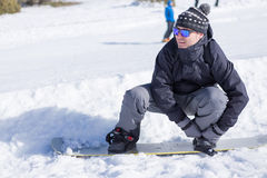 Man putting on snowboard Royalty Free Stock Image
