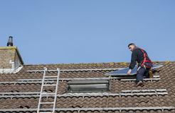 Man putting the solar panel on the roof Royalty Free Stock Photo