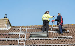 Man putting the solar panel on the roof. Man putting the solar panel to the metal construction on the roof Stock Image
