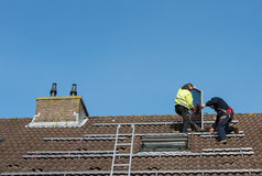 Man putting the solar panel on the roof. Man putting the solar panel to the metal construction on the roof Royalty Free Stock Images
