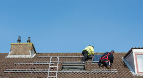 Man putting the solar panel on the roof. Man putting the solar panel to the metal construction on the roof Royalty Free Stock Photography