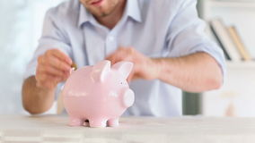Man putting some coins into a piggybank. At home stock footage