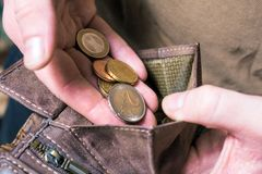 Man Putting Some Euro Coins In His Wallet. Man Putting Euro Coins In His Wallet royalty free stock photography