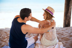 Man putting some lotion on her girlfriend. Rear view of a young men helping his girlfriend by putting on her some sun tan lotion at the beach royalty free stock photography