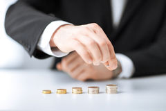 Man putting stack of coins into one row Stock Image