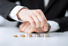 Man putting stack of coins into one row Royalty Free Stock Photography