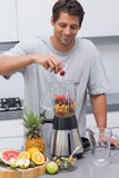 Man putting a strawberry in the blender Stock Photo
