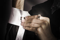 Man putting stylish cuff links on his shirt Royalty Free Stock Image