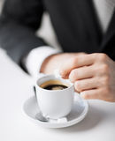 Man putting sugar into coffee Royalty Free Stock Images