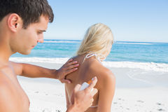 Man putting sun cream on girlfriends back Royalty Free Stock Photos