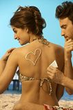 Man putting sunscreen on back of woman in swimsuit Royalty Free Stock Images