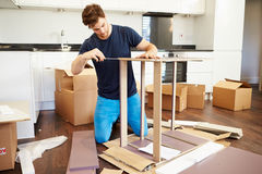 Man Putting Together Self Assembly Furniture In New Home. By Himself Concentrating Stock Photography