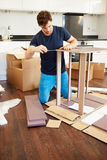 Man Putting Together Self Assembly Furniture In New Home. Kneeling On Floor Using Screwdriver stock images
