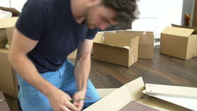 Man Putting Together Self Assembly Furniture In New Home. Man sitting on the floor and following furniture assembly instructions.Shot on Sony FS700 in PAL format stock footage