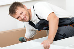 Man putting together self assembly furniture Stock Photo