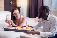 Man putting tray with breakfast on bed Stock Images