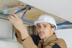 Man putting up suspended ceiling Stock Photos