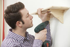 Man Putting Up Wooden Shelf At Home Using Electric Cordless Dril. Man Putting Up Shelf At Home Using Electric Cordless Drill royalty free stock photography