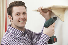 Man Putting Up Wooden Shelf At Home Using Electric Drill Stock Image
