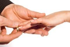 Man putting wedding ring on bride's finger. Man hand putting ring on bride's finger stock images