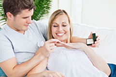 Man putting a wedding ring on his girlfriend's Stock Photo