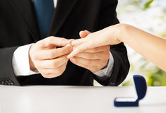 Man putting  wedding ring on woman hand Royalty Free Stock Images