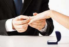 Man putting  wedding ring on woman hand Royalty Free Stock Image
