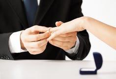 Man putting  wedding ring on woman hand Royalty Free Stock Image