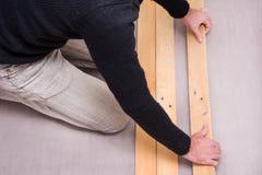 Man putting wood floor Stock Image