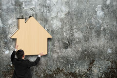 Man putting wooden house into hole of concrete wall Stock Photos