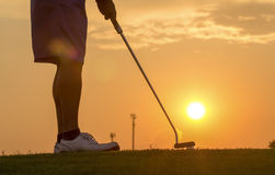 Man puttinging golf against sunset. After work Royalty Free Stock Photography