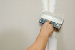 Man putty plasterboard Royalty Free Stock Photo