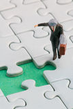 Man puzzle 2. A man is standing in front of a missing jigsaw puzzle piece Stock Photography