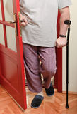 Man in pyjamas with crutch Stock Images
