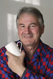 Man in pyjamas holding coffee mug. Man in his fifties wearing red and blue checked pyjamas holding coffee mug and enjoying the start of a new day Royalty Free Stock Images