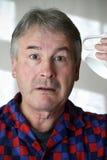 Man in pyjamas holding coffee mug Royalty Free Stock Photography