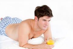 Man in pyjamas holding a glass of orange juice Stock Photography