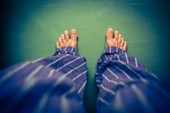 Man in pyjamas looking down on his bare feet Stock Photo
