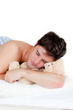 Man in pyjamas sleeping with a teddy-bear. Lying on his bed against white background Royalty Free Stock Images