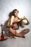 Man with python. One naked person is holding wild albino python, brave man. He smokes a hookah, fruits, passion, desire, feeling, contact of brave human and Stock Image