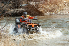 The man on the Quad bike rides on the river with a splashing water Stock Photography